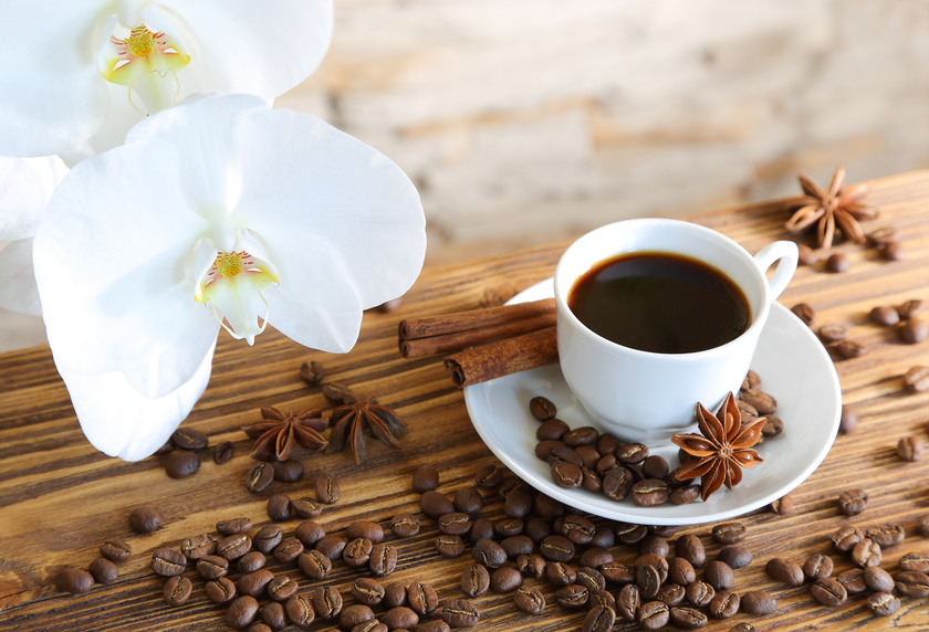 Black coffee with cinnamon on stone wall background and orchids