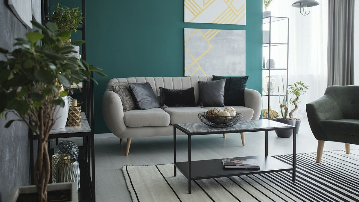 Table on striped carpet in spacious living room interior with sofa against green wall with posters