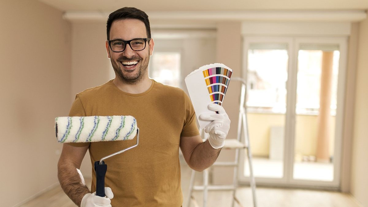 Handsome smiling man holding color palette and painting roller in his hands.