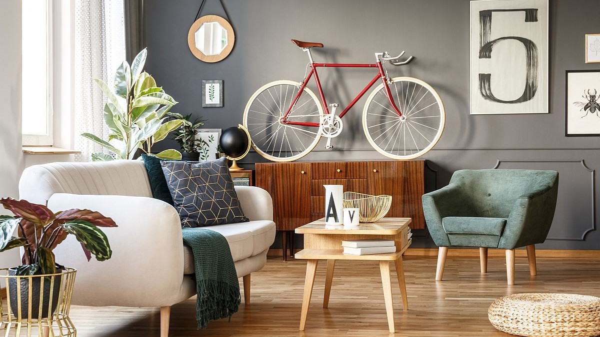 Vintage unique living room interior with good vibes with white comfortable sofa with cushions and blanket and green armchair, cupboard, small table, red bicycle and lots of details including a poster with number five on gray wall